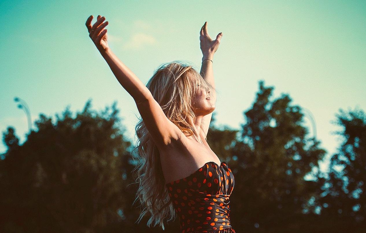 Frau in sommerlicher Umgebung reißt die Arme in die Luft.